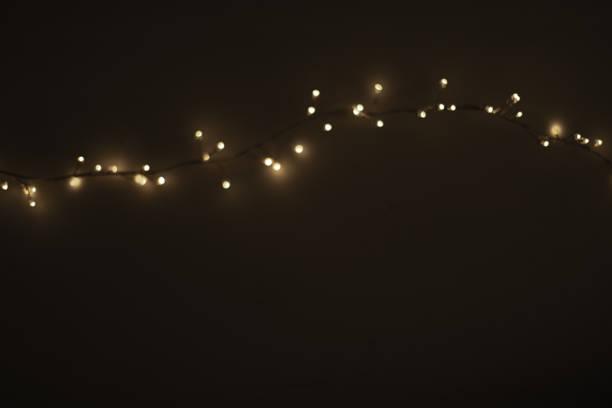 abstract christmas lights on  black  background. defocused  glowing light bulb garland, copyspace - christmas lights imagens e fotografias de stock