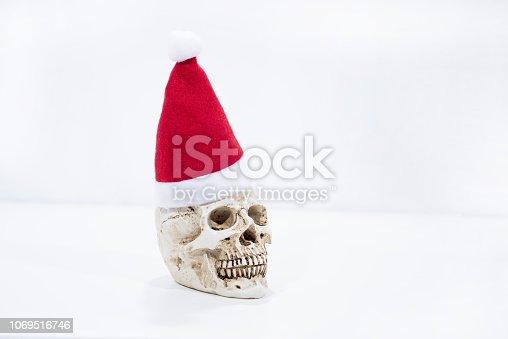 Abstract Christmas photo. Small human skull with Christmas hat on it.