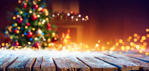 Abstract Christmas - Snowy Table With Bokeh Lights And Defocused Christmas Tree stock photo
