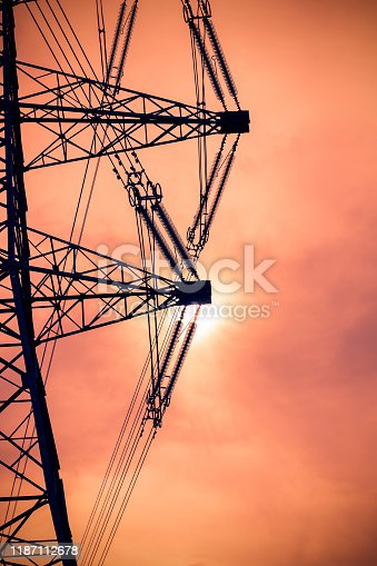 Silhouette of high voltage cables connected to an electricity pylon set against a digitally generated orange coloured sunset sky in England.