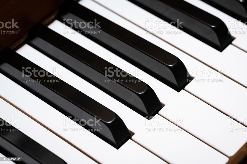 Closeup of piano keys of a light brown piano