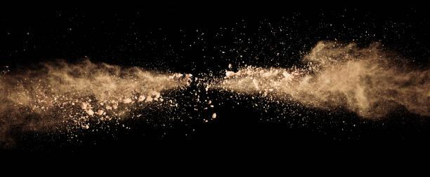 abstract gekleurde bruin poeder explosie geïsoleerd op zwarte achtergrond. - gezichtspoeder stockfoto's en -beelden