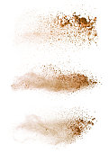 Abstract colored brown powder explosion isolated on white background.