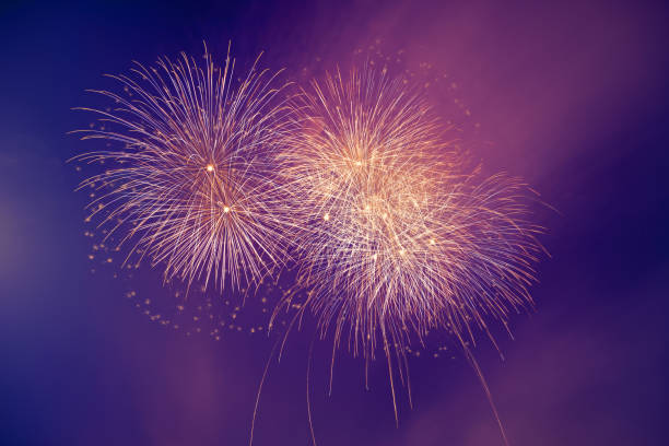 Abstract colorful beautiful fireworks salute against blue sky Abstract colorful beautiful fireworks salute against blue sky. Neon Holographic pattern of salute pyrotechnic effects stock pictures, royalty-free photos & images