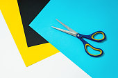 Abstract colour paper and colourful papers background with scissors on top. Sheets of coloured paper for drawing and school. White space for text with colourful paper arrange as frame