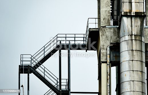 istock Abstract colourless picture of an iron staircase next to an aluminium pipe at the tower of an industrial plant 1223998425