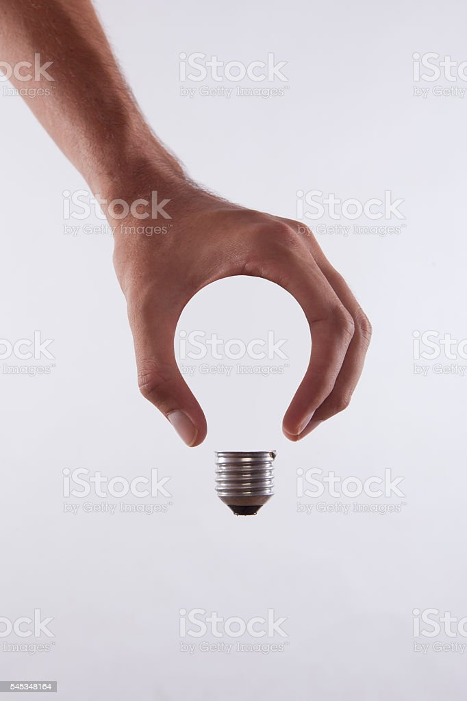 abstract conceptual, male's hand holding a light bulb stock photo