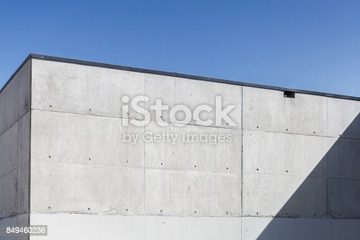 Abstract concrete interior, corner of grungy walls under blue sky