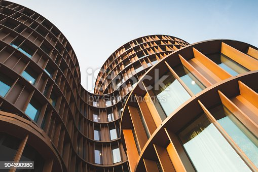 Abstract contemporary architecture background, round towers made of yellow shiny metal and glass