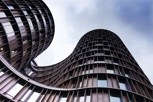 Low angle shot of Axel Towers Copenhagen on a cludy day in Copenhagen, Denmark. Axel Towers Copenhagen is an abstract contemporary architectural office building and consists of five cylindrical towers consisting of metal, copper and glass.
