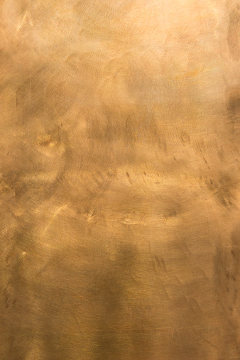 Brushed brown-golden copper or bronze surface, with visible brush strokes. The sheet metal has an appealing cloudy, wavy texture. Vertical orientation. The image has been shot outdoors during natural day light, full frame and close up. Ideal for backgrounds. The size of the photo is 4912 x 7360 px. High resolution.