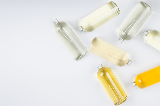 Abstract cosmetic border of lying bottles with different pale colors liquid, silver cap on white background, top view, copy space.