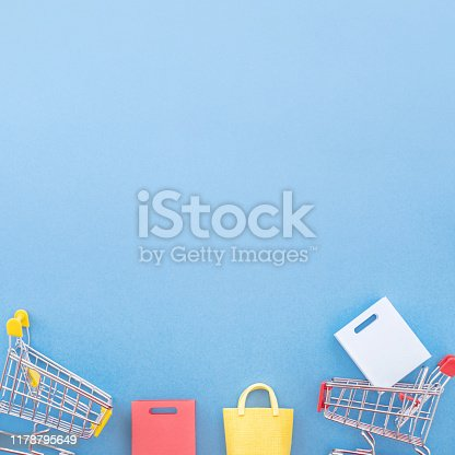 995719694 istock photo Abstract design element, annual sale, shopping season concept, mini yellow cart with colorful paper bag on pastel blue background, top view, flat lay 1178795649
