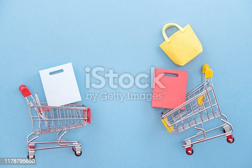 995719694 istock photo Abstract design element, annual sale, shopping season concept, mini yellow cart with colorful paper bag on pastel blue background, top view, flat lay 1178795650
