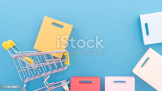 995719694 istock photo Abstract design element, annual sale, shopping season concept, mini yellow cart with colorful paper bag on pastel blue background, top view, flat lay 1178795671