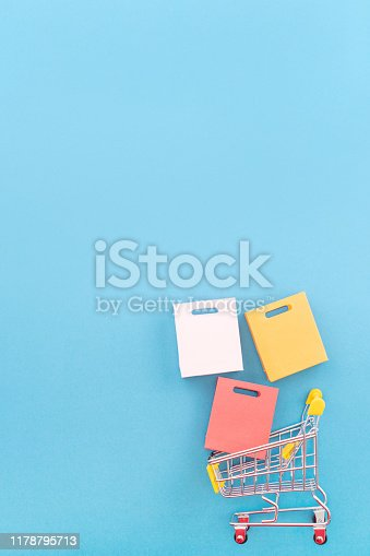 istock Abstract design element, annual sale, shopping season concept, mini yellow cart with colorful paper bag on pastel blue background, top view, flat lay 1178795713