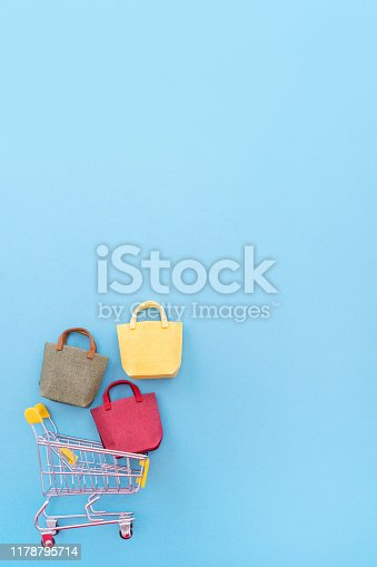 995719694 istock photo Abstract design element, annual sale, shopping season concept, mini yellow cart with colorful paper bag on pastel blue background, top view, flat lay 1178795714