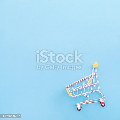 995719694 istock photo Abstract design element, annual sale, shopping season concept, mini yellow cart with colorful paper bag on pastel blue background, top view, flat lay 1178795717