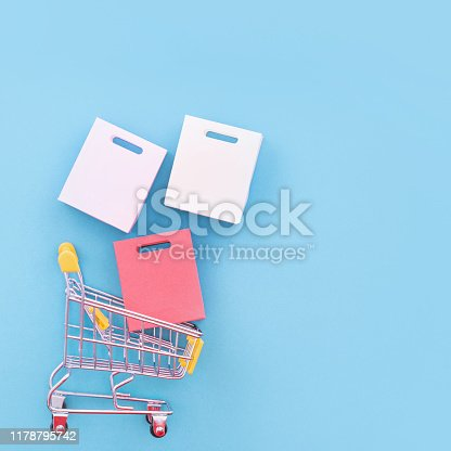 995719694 istock photo Abstract design element, annual sale, shopping season concept, mini yellow cart with colorful paper bag on pastel blue background, top view, flat lay 1178795742