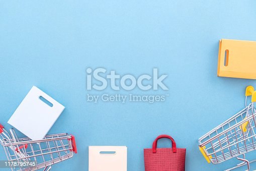 995719694 istock photo Abstract design element, annual sale, shopping season concept, mini yellow cart with colorful paper bag on pastel blue background, top view, flat lay 1178795745