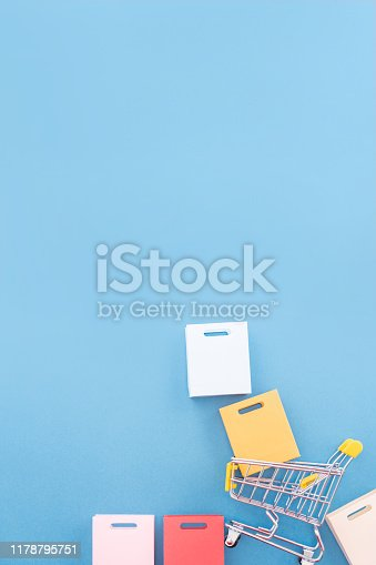 995719694 istock photo Abstract design element, annual sale, shopping season concept, mini yellow cart with colorful paper bag on pastel blue background, top view, flat lay 1178795751