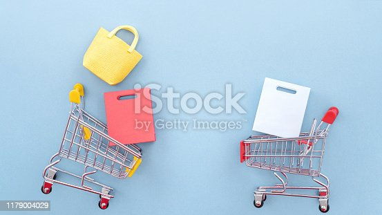 995719694 istock photo Abstract design element, annual sale, shopping season concept, mini yellow cart with colorful paper bag on pastel blue background, top view, flat lay 1179004029