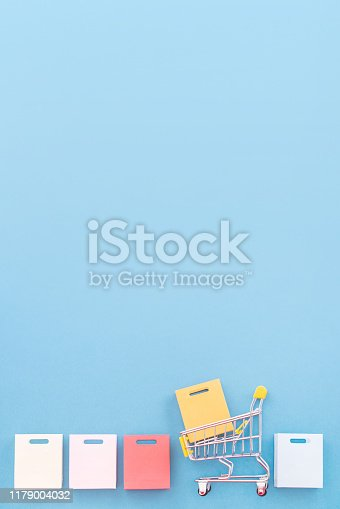 995719694 istock photo Abstract design element, annual sale, shopping season concept, mini yellow cart with colorful paper bag on pastel blue background, top view, flat lay 1179004032