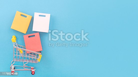 995719694 istock photo Abstract design element, annual sale, shopping season concept, mini yellow cart with colorful paper bag on pastel blue background, top view, flat lay 1179004048