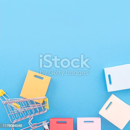 995719694 istock photo Abstract design element, annual sale, shopping season concept, mini yellow cart with colorful paper bag on pastel blue background, top view, flat lay 1179004049