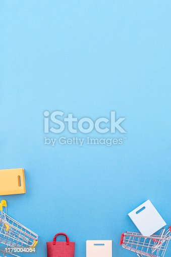 995719694 istock photo Abstract design element, annual sale, shopping season concept, mini yellow cart with colorful paper bag on pastel blue background, top view, flat lay 1179004054
