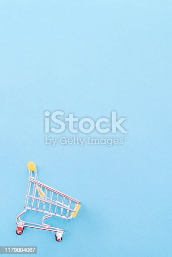 995719694 istock photo Abstract design element, annual sale, shopping season concept, mini yellow cart with colorful paper bag on pastel blue background, top view, flat lay 1179004067