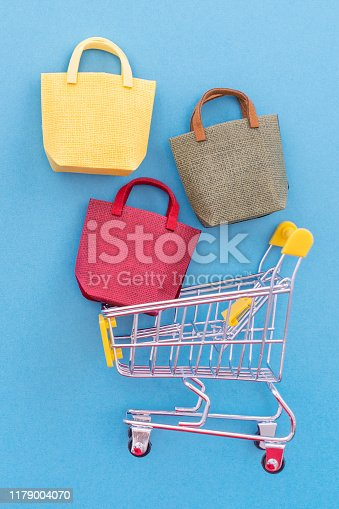 995719694 istock photo Abstract design element, annual sale, shopping season concept, mini yellow cart with colorful paper bag on pastel blue background, top view, flat lay 1179004070