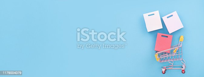 995719694 istock photo Abstract design element, annual sale, shopping season concept, mini yellow cart with colorful paper bag on pastel blue background, top view, flat lay 1179004079