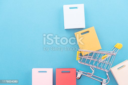 995719694 istock photo Abstract design element, annual sale, shopping season concept, mini yellow cart with colorful paper bag on pastel blue background, top view, flat lay 1179004080