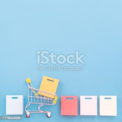 995719694 istock photo Abstract design element, annual sale, shopping season concept, mini yellow cart with colorful paper bag on pastel blue background, top view, flat lay 1179004093