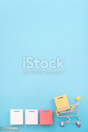 istock Abstract design element, concept of annual sale, shopping season - mini yellow cart with paper bag isolated on pastel blue background. 1177555855