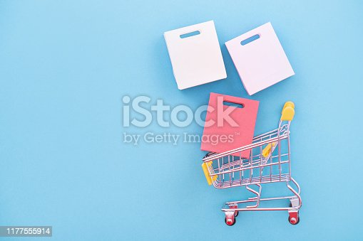 istock Abstract design element, concept of annual sale, shopping season - mini yellow cart with paper bag isolated on pastel blue background. 1177555914