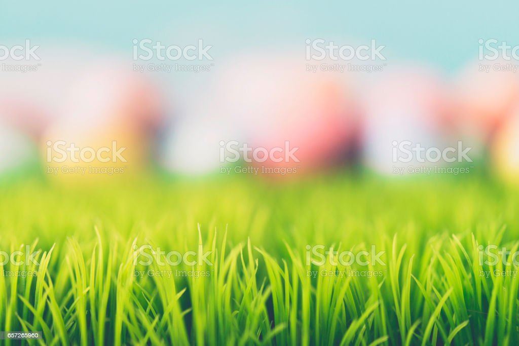 Abstract Easter background with hand painted eggs and grass stock photo