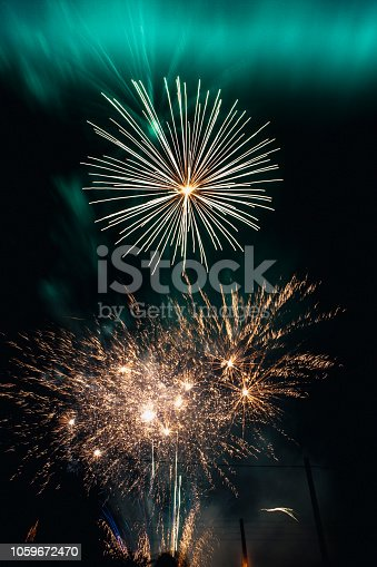 A close-up shot of bright fireworks in the sky on a cold night, the fireworks resemble celebrations.