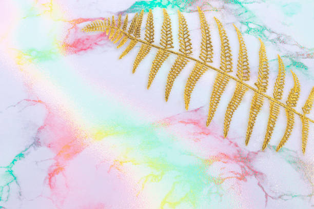 Abstract flowing Ink, gold fern leaf, palm frond on multicolored marble background. Trendy creative design. Abstract flowing Ink, gold fern leaf, palm frond on multicolored marble background. Trendy creative design glossa stock pictures, royalty-free photos & images