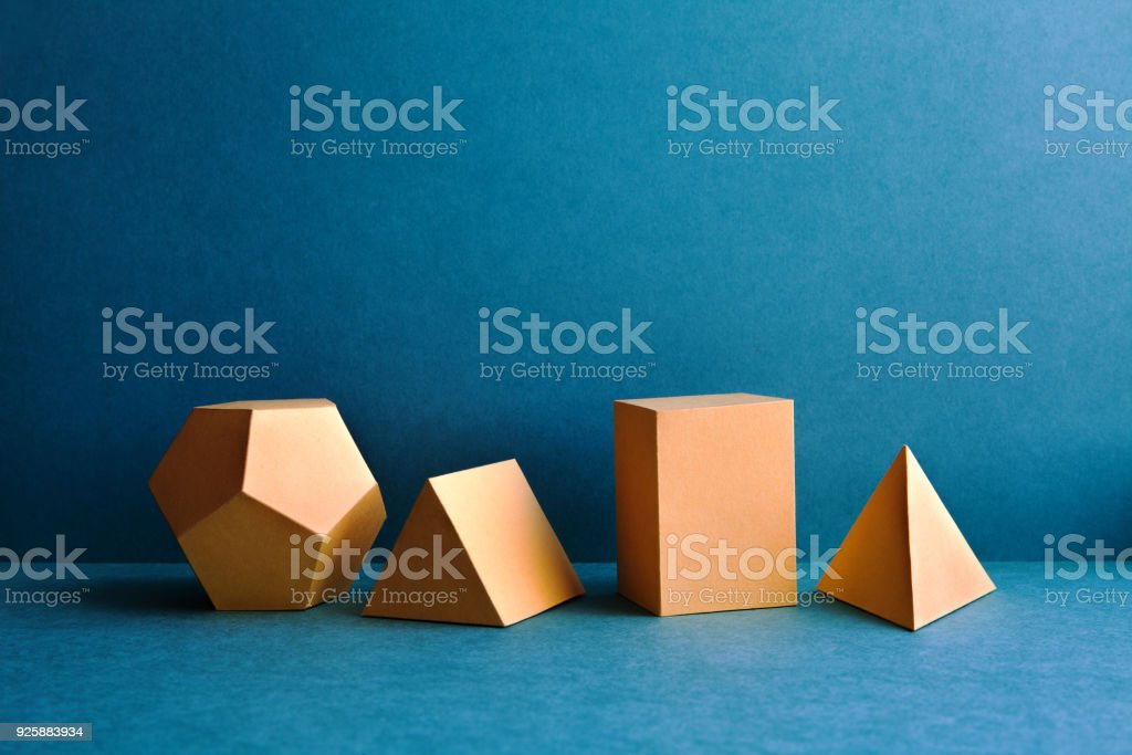 Abstract geometric figures. Three-dimensional dodecahedron pyramid tetrahedron cube rectangular objects on blue background. Yellow color Platonic solids still life background stock photo