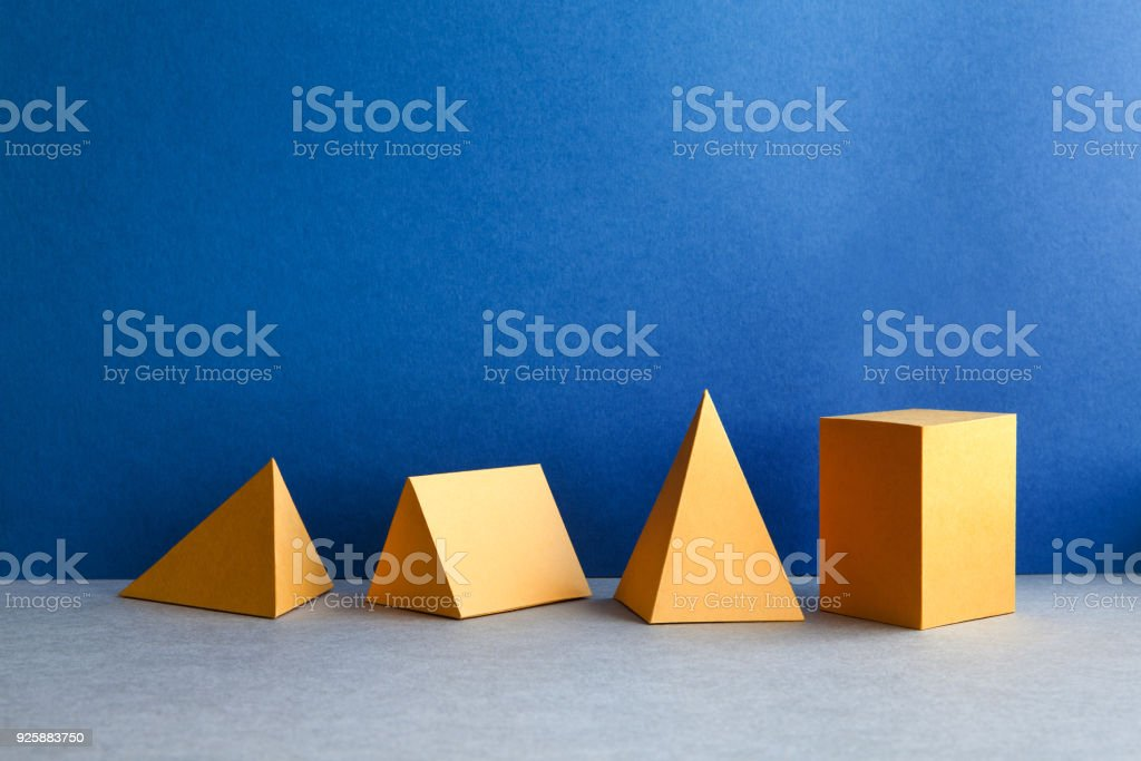 Abstract geometric figures. Three-dimensional pyramid tetrahedron cube rectangular objects on blue gray background. Yellow color Platonic solids still life background stock photo