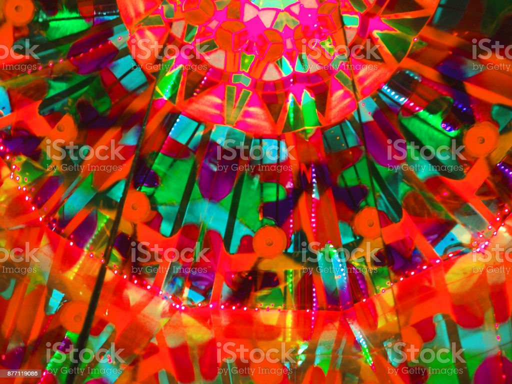 Abstract geometric pattern formed by refractions in a kaleidoscope, psychedelic background. Basis of the red and green tones stock photo