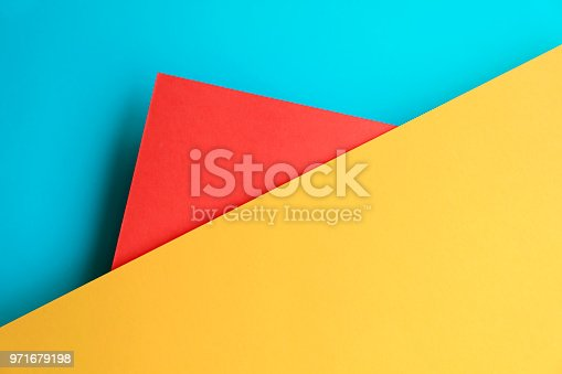 istock Abstract geometricpaper background in soft pastel blue red and yellow colors 971679198