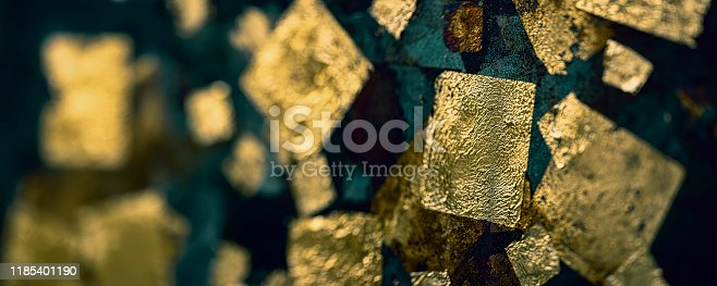 Abstract textured background of gold leaf square shapes on a grungy old rusty weathered metal background.