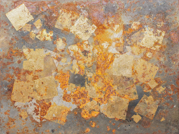 Abstract, gold leaf background on a rusty metal surface. stock photo