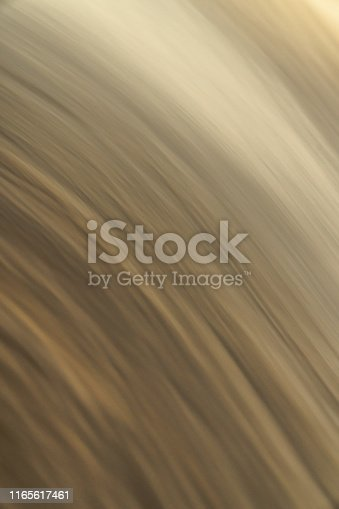 Abstract gold or beige yellow colored photograph long exposure of water w/ blurred curved streaks or ripples texture making a great creative background gradient or backdrop wallpaper image.