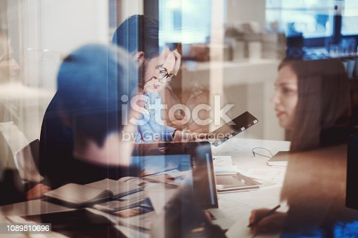Abstract group of business people in the meeting. Laptop-digital-tablets are off, those are visible reflections.