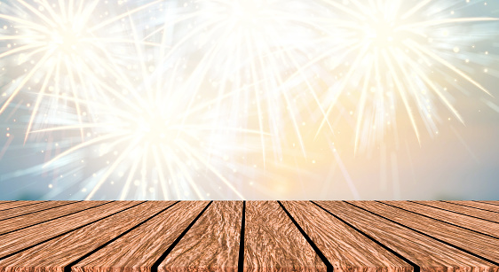 abstract group of exploding fireworks with multi vibrant colorful on night sky with brown wooden plank deck background for show and promote your content product or celebration about merry happy new year 2019 ,diwali,labor's day ,independence's day concept