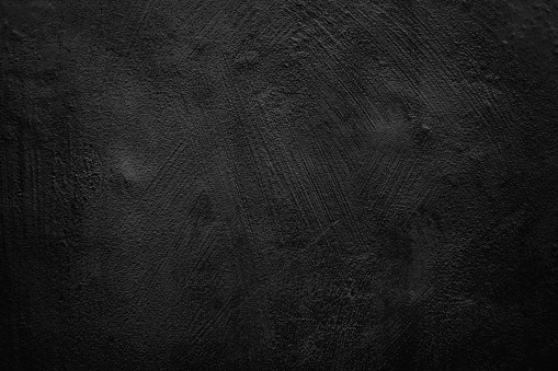Close up on cement plaster wall, black colored in grunge style.
